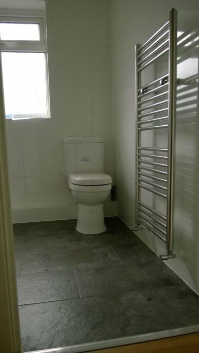 dark floor tiles, heated rail, toilet